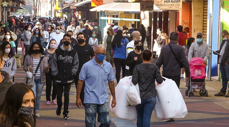 #PraCegoVer Pessoas de máscaras andando na rua