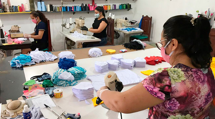 #PraCegoVer Imagem de confecção com costureiras nas máquinas produzindo máscaras em primeiro plano uma senhora corta as máscaras no pano