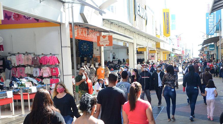 #PraCegoVer Pedestres caminham nas ruas, usando máscaras de proteção, para aproveitar a reabertura do comércio
