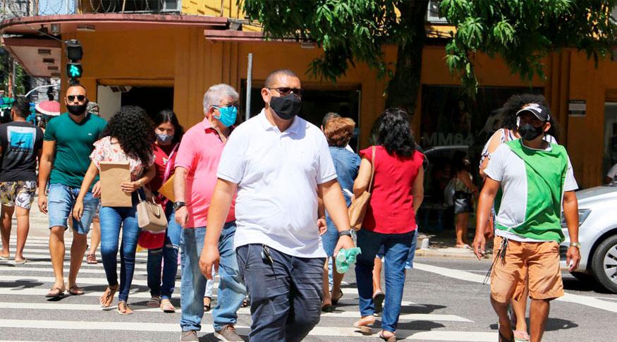 #PraCegoVer Pessoas de máscaras atravessam a rua. Em primeiro plano um homem barrigudo de camisa branca e máscara preta