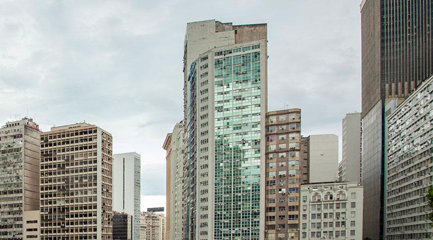 #PraCegoVer Fachada de prédios comerciais com o céu com nuvens brancas
