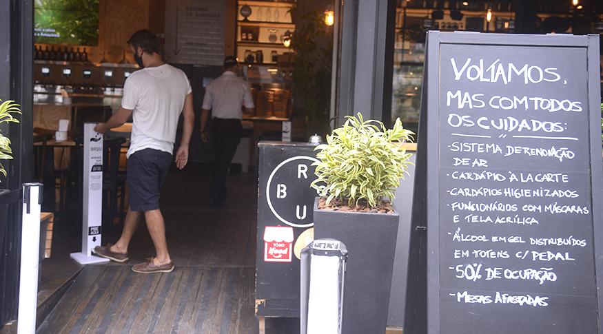 #PraCegoVer A foto mostra um pequeno restaurante, do lado direito, um quadro com o cardápio e do aldo esquerdo, um rapaz de costas entrando no lugar.