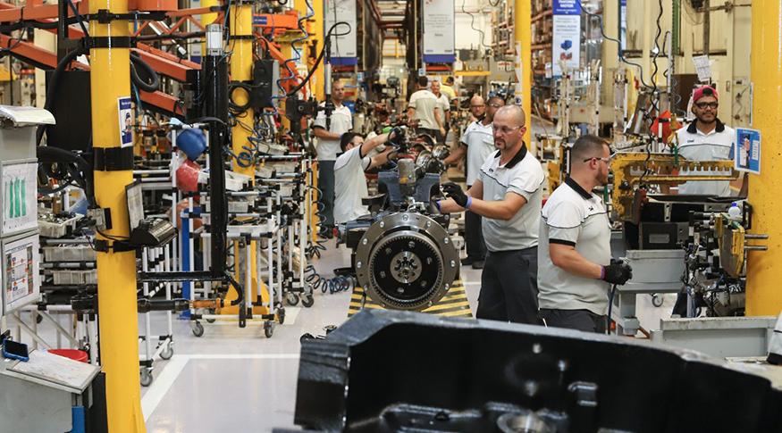 #PraCegoVer A foto mostra o interior de uma indústria, com operários trabalhando