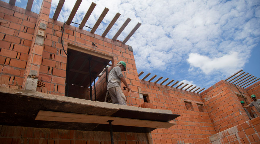 #PraCegoVer A foto mostra a parte de cima de uma obra em andamento, ainda na fase de colocação de telhas