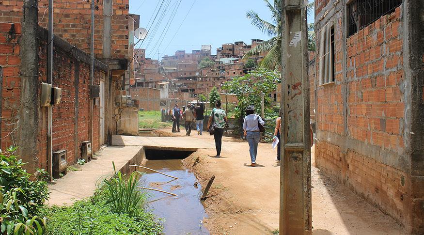 #PraCegoVer a foto mostra uma rua sem calçamento com esgoto a céu aberto