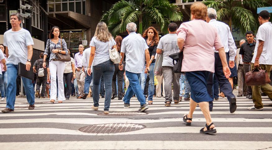#PraCegoVer pessoas atravessando a rua na faixa de pedestre