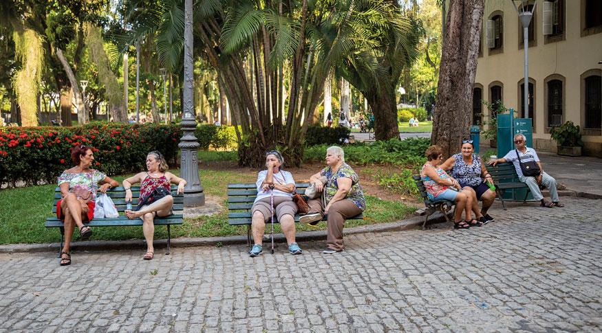 #PraCegoVer a foto mostra uma praça com idosos sentados em bancos de madeira