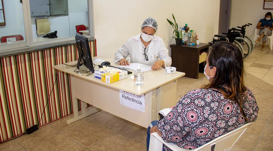 #PraCegoVer A foto mostra uma sala de atendimento médico, em que a profissional de saúde está vestida de branco e usando EPIs e a mulher que está sendo atendida, está usando uma máscara branca. Ambas estão sentadas.