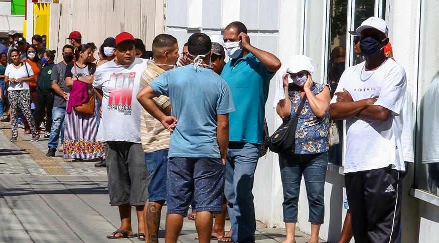 #PraCegoVer pessoas em fila na rua para sacar o auxílio emergencal