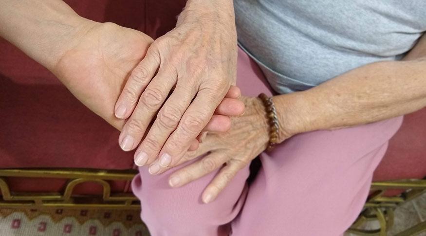 #PraCegoVer A foto mostra uma mão de uma pessoa adulta entrelaçada na mão de uma pessoa idosa, apoiadas no colo da pessoa idosa
