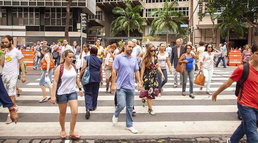 #PraCegoVer A foto mostra vária pessoas atravessando uma rua movimentada no Centro do Rio de Janeiro