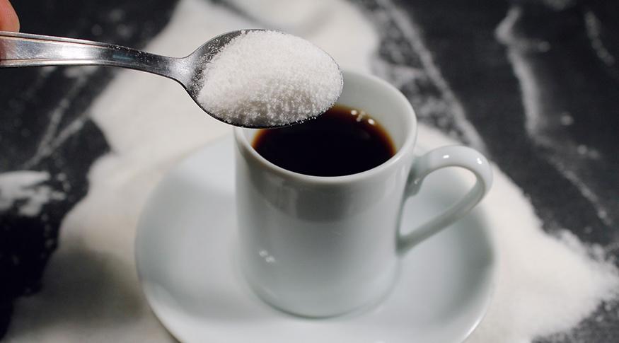 #PraCegoVer A foto mostra uma colher de açucar cheia que será colocada numa xícara de café