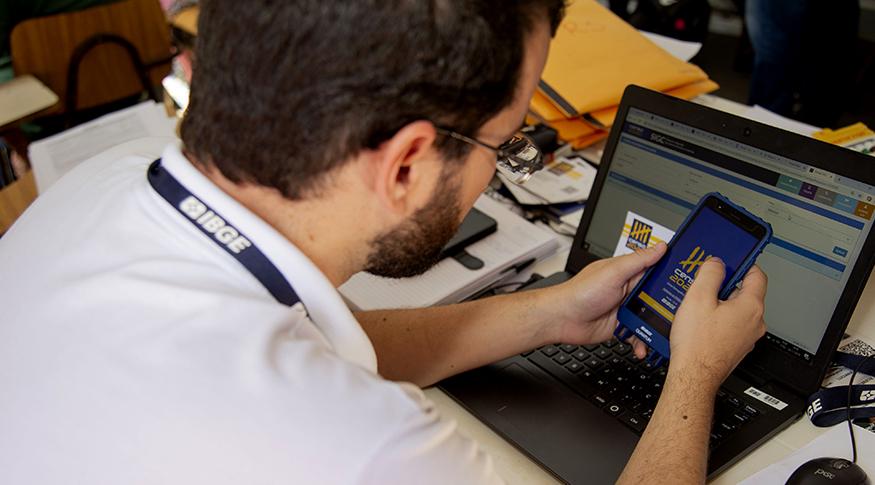 #PraCegoVer A foto mostra um servidor do IBGE sentado em sua mesa de trabalho, de costas, testando um dispositivo móvel de coleta do Censo 2020