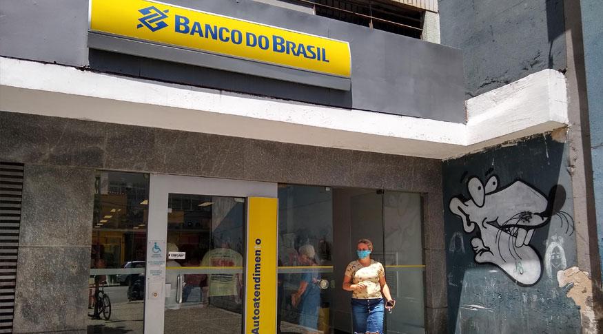 #PracegoVer Fachada do Banco do Brasil com uma mulher usando saia jeans e blusa rosa e máscara saindo da agencia. Na parede ao lado direito um grafite de um rato